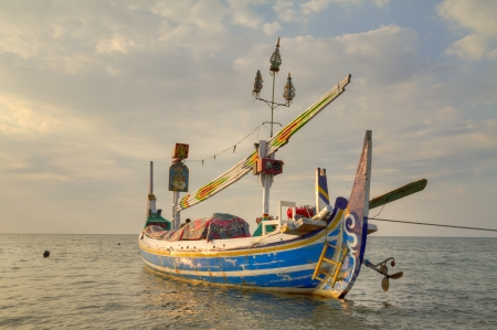 Lovina, August, 23, 2011 - Colorful  handcrafted Balinese wooden fishing boat moored with rope during golden hour of sunset with cloudy background Editorial