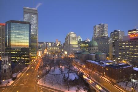 Kanada, Montreal, december 12, 2012 - Sunrise tükrözi felhőkarcolók és egyházi mentén Place du Canada hóban