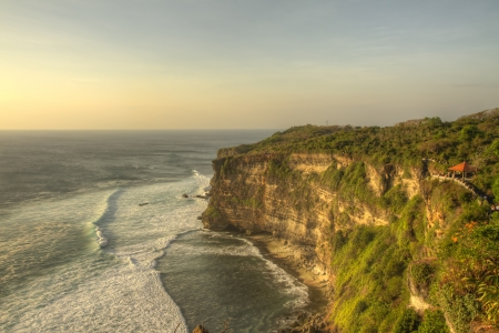Sunset over high cliffs at Uluwatu temple on Bali, Indonesia, with golden limestone rocks and impressive waves on the sea