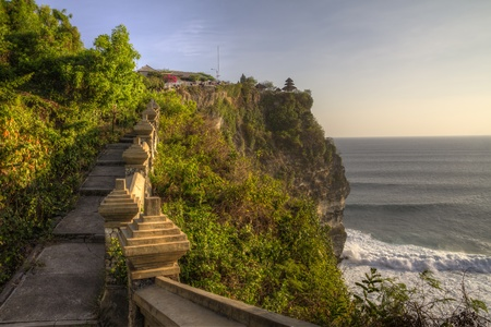 Paved path with ancient stone fencing towards Uluwatu temple on high cliff in Bali, Indonesia, at dusk, against ocean background