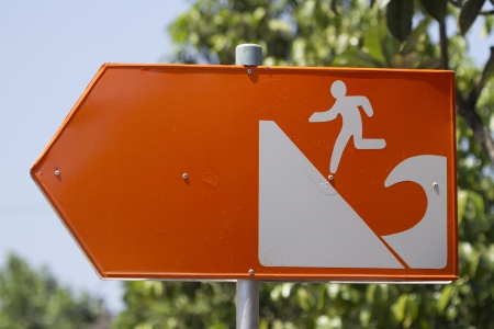 Tsunami warning sign in orange gives direction to safety on higher grounds in Sanur, Bali, Indonesia