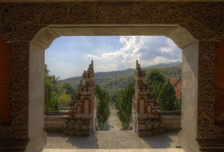 Buddhist temple on Bali: View through two gates, an ornamented stone entry gate and a split gate towards forest on hill at Brahma Vihara Arama Buddhist Monastery in Buleleng Stock Photo