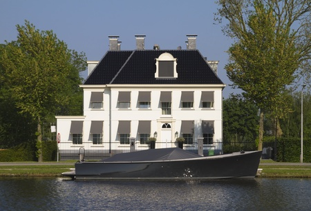 Dutch retro-styled villa at river Amstel near Amsterdam, newly built with black motor boat in front of the house Editorial