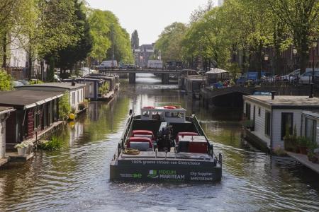 Amsterdam, Nieuwe Prinsengracht, június 7, 2013: Mokum Mariteam elektromos áruszállító hajóval szolgáltatások Amszterdam csatornáin powered by megújuló energia