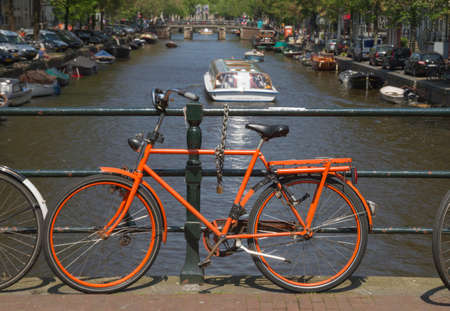 Dutch orange bike on canal bridge in Amsterdam with canal boat on background