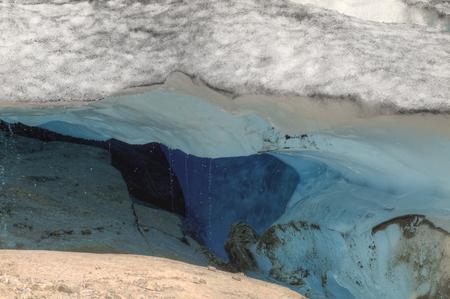 breen: grotta del ghiacciaio con ghiaccio blu scuro all'interno e l'acqua di fusione a causa delle temperature in aumento in ghiacciaio Nigardsbreen, Norvegia