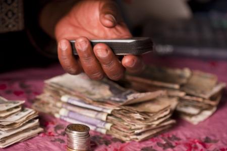 Mikrofinanszírozási találkozó, számolás afrikai pénzt mobiltelefon Stock fotó