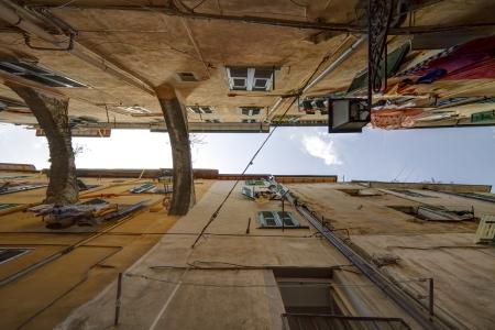 Nagyon szűk utcában régi városközpont San Remo, Olaszország, árkádos tartani a házak egyenesen felfelé, tipikus ablakon redőny és mosoda lóg ki az ablakon