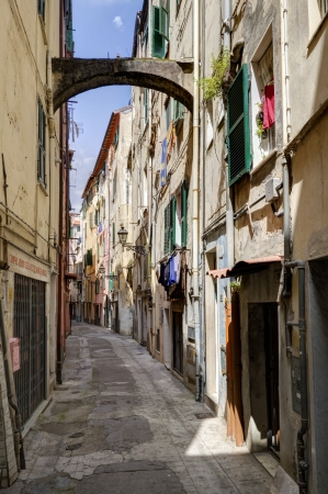 Nagyon szűk utcában régi városközpont San Remo, Olaszország, árkádos tartani a házak egyenesen felfelé