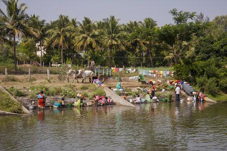 Színes ruhákat, hogy kézzel mosni és szárítani Cauveri folyó közelében Mysore a Karnakata, India, egy ökör kocsira elhaladó Sajtókép