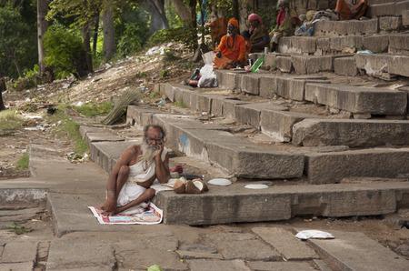 White dressed hinduist Sadhu monk resting on stone steps of Cauveri river