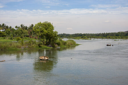 Round coracle boats rowing on wide Cauveri river in Karnataka, India