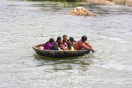 Bamboo-made coracle boat with happy Indian girls recreating on Kaveri river in Karnataka, India