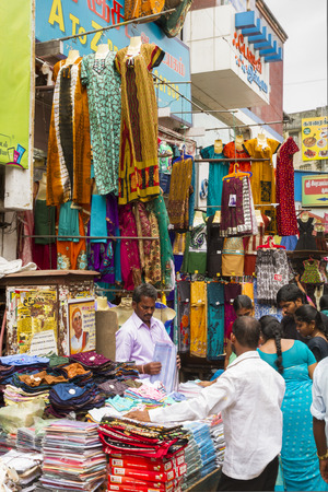 Textile market stalls stacking Indian clothes high up in Chennai, India