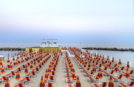 Beach chairs and umbrellas in rows converging into coastal horizon at beach terrace in  San Remo, Italy, Europe in twilight hour Editorial
