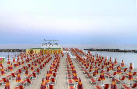 Napernyőkkel és nyugágyakkal sorokban konvergáló a parti horizont strandon terasz San Remo, Olaszország, Európa alkonyi óra