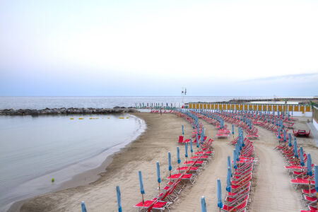 Rows of abandoned beach chairs and umbrellas converging into coastal horizon at beach terrace in  San Remo, Italy, Europe in twilight hour