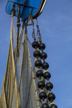 Trawl fishing net for shrimps in water, dragged through Wadden Sea by yellow beam against blue sky