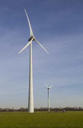 cooperativismo: Dos molinos de viento que entregan la energ�a renovable, propiedad de cooperativa de agricultores, que se encuentra en la tierra hierba verde en la regi�n de Achterhoek de los Pa�ses Bajos, contra el cielo claro Foto de archivo
