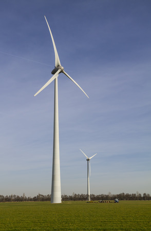 cooperative: Two windmills delivering renewable energy, owned by farmers cooperative, located on green grass land in the Achterhoek region of the Netherlands, against clear sky Stock Photo