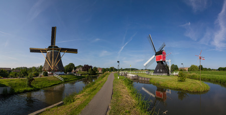 Two colourful Dutch windmills on both sides of biking path, surrounded by canals on a bright spring day in Holland near Utrecht