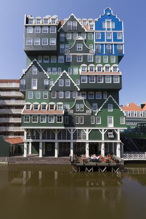 Az excentrikus modern építészet hotel a város központjában Zaandamban álló halmozott homlokzatok jellegzetes holland fából készült zöld nyeregtetős házak, a szálloda vendégei ebédelni a teraszon a víz fölött egy fényes nyári napon