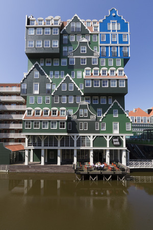 Eccentric modern architecture of hotel in city center of Zaandam, consisting of stacked facades of typical Dutch wooden green gable houses, with hotel guests having lunch on terrace above water on a bright summer day