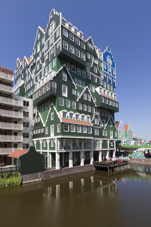 Modern architecture of hotel in city center of Zaandam, consisting of stacked facades of typical Dutch wooden green gable houses, on a bright summer day