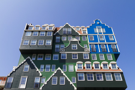 Multiple facades of typical Dutch wooden green gable houses in contemporary hotel architecture Editorial