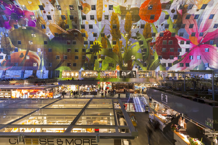 Markthal Rotterdam in vroege avond met marktkramen en kunstwerk Hoorn des Overvloeds op boogvormig plafond