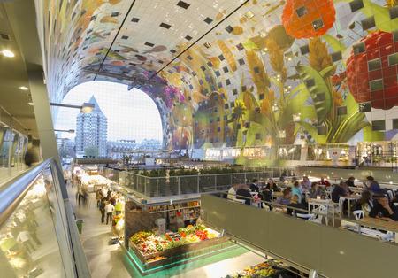 Markthal Rotterdam in vroege avond met marktkramen en kunstwerk 'Hoorn des Overvloeds' op boogvormig plafond