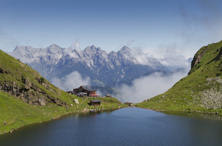 Mountain lodge Wildseeloderhaus majestically set at the edge of the Karsee mountain lake with view on Kitzbuheler Alps. Outdoor tourists are hiking along the lake.