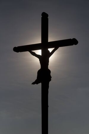 Christian Crucifix with the sun providing an aura to the head of statue of Jesus Christ on the cross