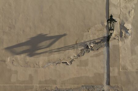 Old street lantern throws long shadow on flaking medieval wall at Prague Castle in Czech Republic