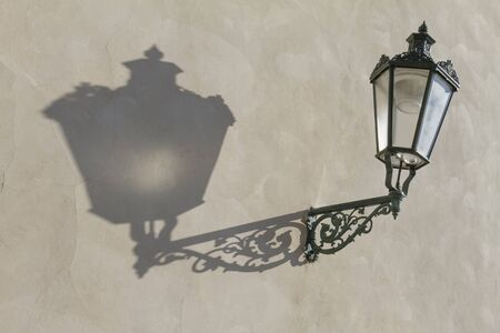 Antique street lantern throws straight shadow on painted wall at Prague Castle in Czech Republic