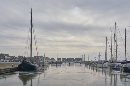 Marken, The Netherlands - March 3, 2018: Sailboats in frozen harbor of the old island Marken, with Dutch skaters enjoying the golden wooden houses. Editorial