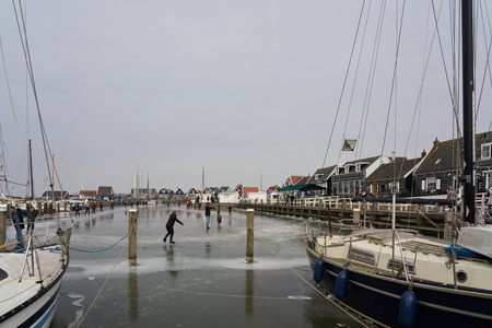 Marken, The Netherlands - March 3, 2018: Dutch ice skaters preparing to skate during winter in the old picturesque harbor of the island Marken, amidst boats and old, green wooden houses Stock Photo - 106981380