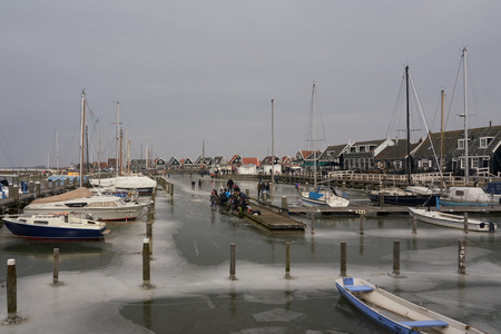 Marken, The Netherlands - March 3, 2018: Dutch ice skaters preparing to skate during winter in the old picturesque harbor of the island Marken, amidst boats and old, green wooden houses