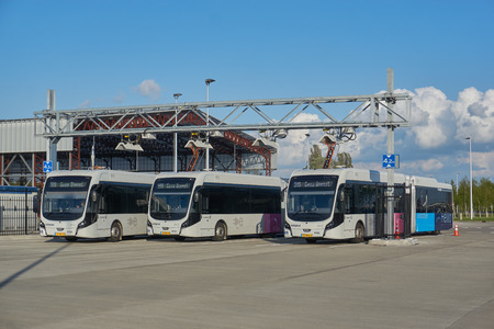 Electric buses charging energy at Schiphol Airport, the Netherlands, as part of sustainable public transport program Stock Photo - 106981712