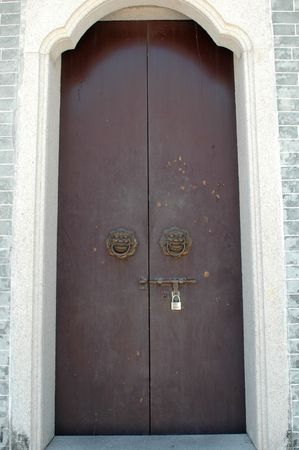 Entrance door to temple in China, made of wood with special holder in shape of lion face. photo