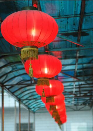 Red lantern, shining, typical Chinese decorations for new year. Hanged under the blue roof. Stock Photo