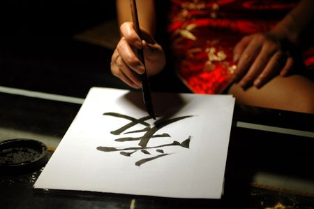 Chinese handwriting, art of calligraphy. Sign Ai - means LOVE. Written by femal in traditional Chinese dress.