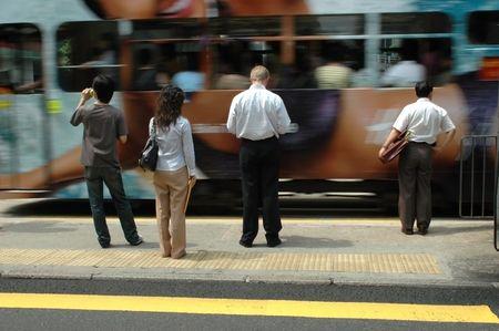 People in Hongkong waiting for green light, tram passing.