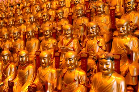 China, Shanghai city. Longhua Temple. Hundreds of golden buddhas sculptures having gathering inside temple.