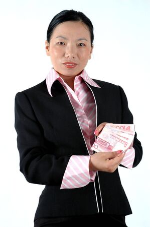 asian office lady: Asian office lady holding Chinese money, RMB banknotes, counting money, wearing elegant suit.