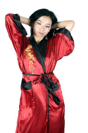 Pretty asian girl just awake, wearing red dressing gown with golden dragon. photo