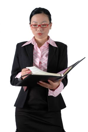 reviewing documents: Chinese businesswoman, wearing ladys suit and shirt.  Holding documents, reviewing documents.