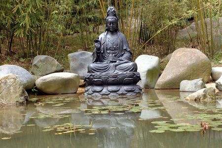 Buddha sculpture surrounded by water from small pond with lotus flowers and bamboo trees. photo