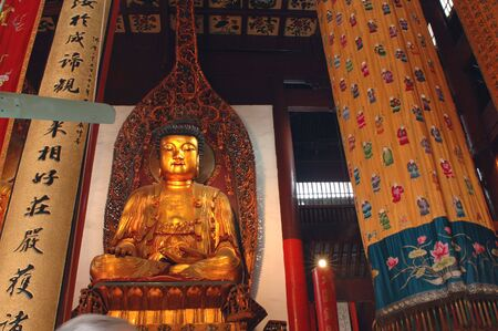 jade buddha temple: Indoor photo of buddhist temple with traditional sculptures of different buddha in golden color. Jade Buddha Temple in Shanghai. Stock Photo