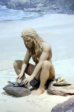 Prehistoric homosapiens sculpture in Hongkong museum. Male using simple tools and preparing fish. Stock Photo